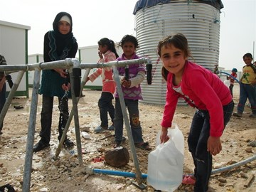 A family collecting water from a tap stand in Zaatari refugee camp.